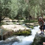 Boy standing on rock next to river banked with green trees in Ihlara Valley, Cappadocia, Turkey