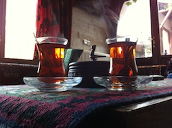 Two hour-glass shaped tea glasses full of steaming tea in cappadocia